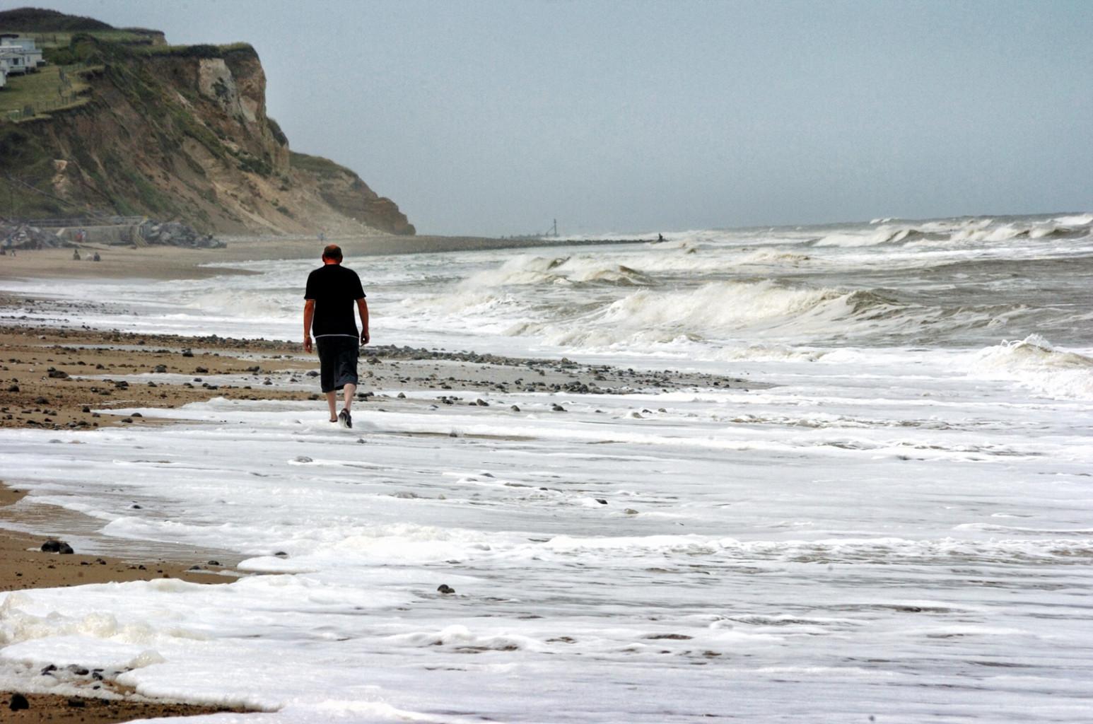 man walking along the beach near Cromer in Norfolk, UK